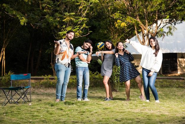 Ragazze asiatiche indiane che prendono in giro i ragazzi sconfitti negli sport di calcio, celebrando la vittoria
