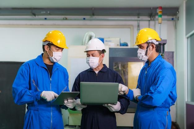 Gli ingegneri industriali asiatici e il lavoratore in elmetti discutono della linea di prodotti nel laptop e fanno gesti dimostrativi e lavorano in una fabbrica di produzione di industria pesante.