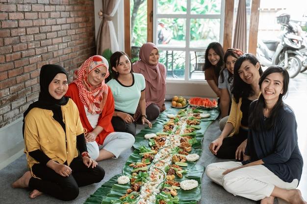 Cibo tradizionale javanese asiatico che si siede insieme sul pavimento