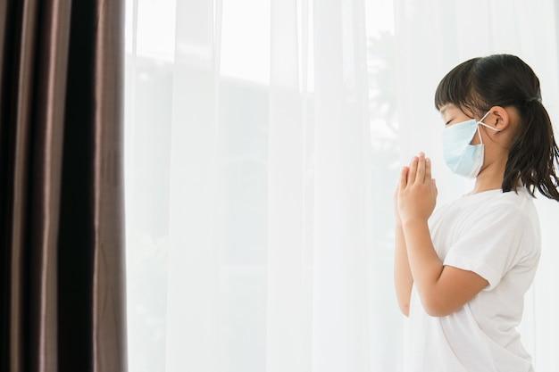 Bambina asiatica che prega indossando una maschera per proteggere pm2.5 e covid-19 bambina che prega a mano