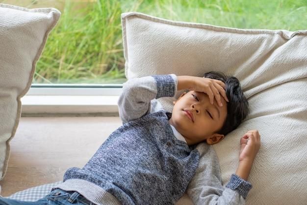 Il bambino asiatico soffre di mal di testa a causa della sua malattia.