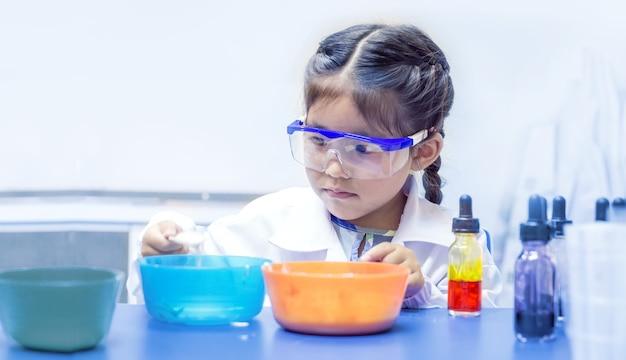 Bambino asiatico che impara chimica con te stesso in classe di laboratorio chimico sul tavolo
