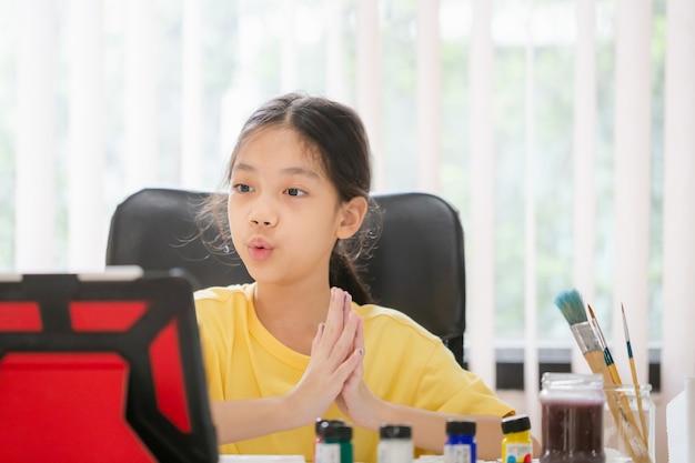 Studente asiatico studente online studio di classe, bambino che dipinge a tavola nella stanza dei giochi, ragazza che impara il corso creativo di disegno artistico online a casa