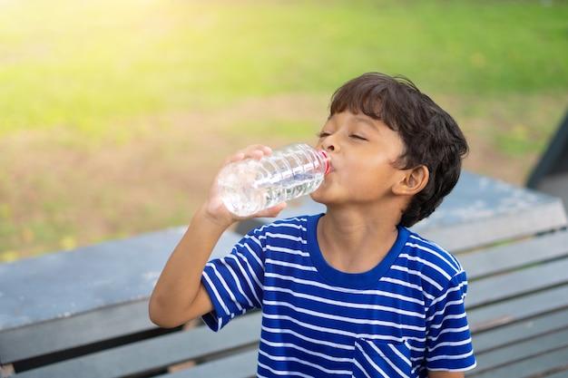 Bambino asiatico assetato di acqua e acqua potabile da una bottiglia di plastica trasparente nel parco.