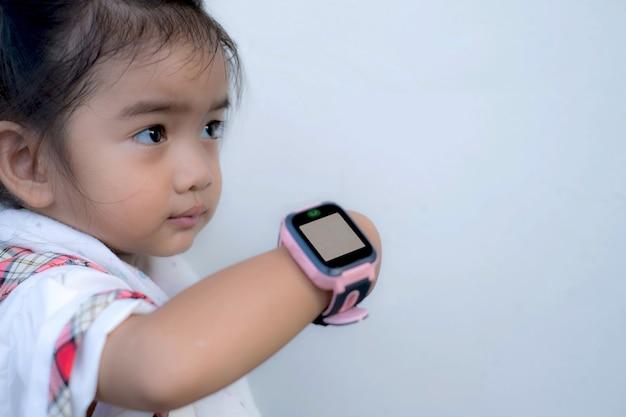 Il bambino asiatico usa orologi intelligenti di tecnologia con facce felici