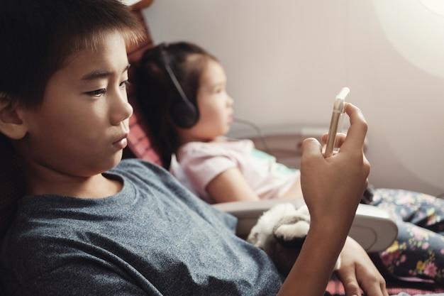 Bambini asiatici utilizzando smart phone in volo