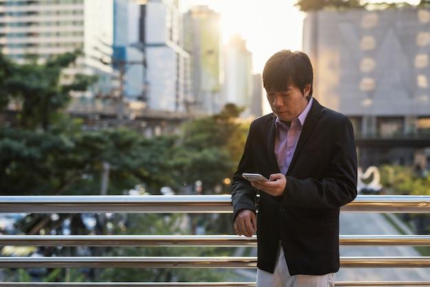 Uomo d'affari asiatico ceo coreano, 40 anni o uomo di mezza età, testo sullo smartphone per discutere del piano di progetto aziendale all'esterno dell'edificio per uffici al tramonto. utilizza l'applicazione aziendale per la comunicazione.