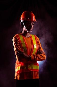 Le donne lavoratrici asiatiche indossano un cappello duro e una protezione ampia in tonalità arancione