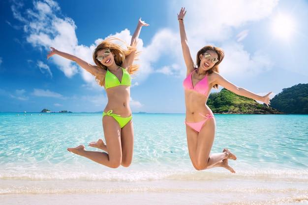 Signore asiatiche in costume da bagno che salta sulla spiaggia