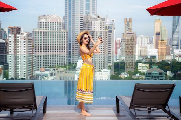 Signora asiatica gode di selfie in piscina sul tetto dell'hotel nella città di bangkok, thailandia