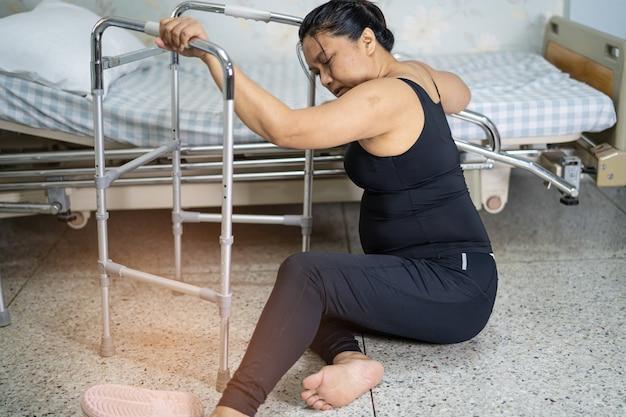 Signora asiatica che cade usa il camminatore nel soggiorno perché superfici scivolose.