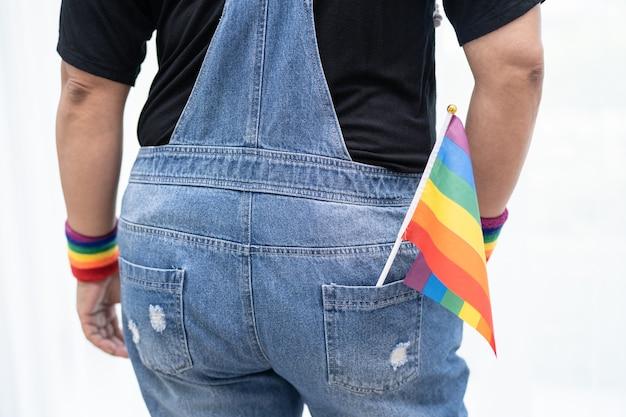 Signora asiatica che tiene bandiera di colore arcobaleno simbolo del mese dell'orgoglio lgbt