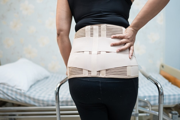 Paziente di signora asiatica che indossa cintura di supporto per il dolore alla schiena per lombare ortopedico con deambulatore.