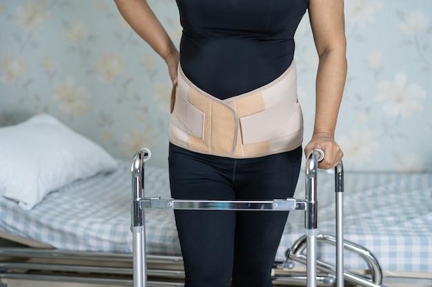 Paziente asiatico che indossa cintura di supporto per il dolore alla schiena per lombare ortopedico con deambulatore.