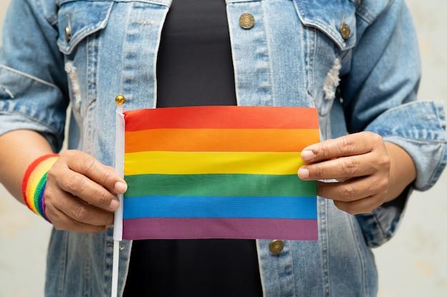 Signora asiatica che indossa giacca di jeans blu o camicia di jeans e in possesso di bandiera color arcobaleno, simbolo del mese di orgoglio lgbt.