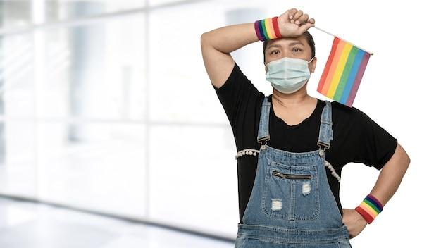Signora asiatica che indossa una maschera per proteggere il virus covid19 che tiene la bandiera arcobaleno simbolo del mese dell'orgoglio lgbt