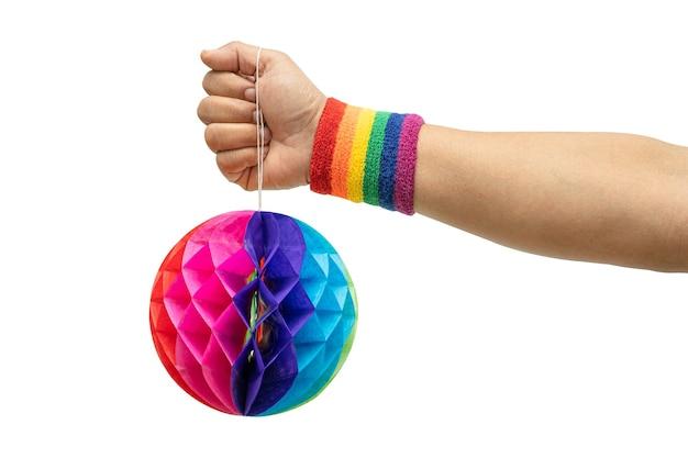 Signora asiatica che indossa braccialetti con bandiera arcobaleno che tengono palla di fiori di carta colorata a nido d'ape isolata su sfondo bianco con tracciato di ritaglio, simbolo del mese dell'orgoglio lgbt.