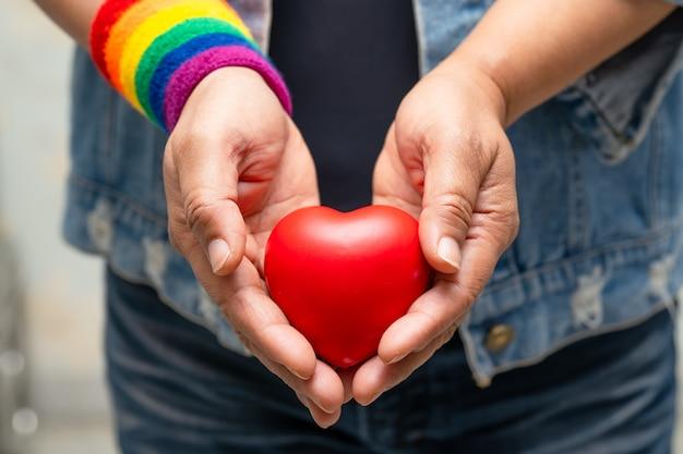 Signora asiatica che indossa braccialetti arcobaleno e tiene un cuore rosso, simbolo del mese dell'orgoglio lgbt.