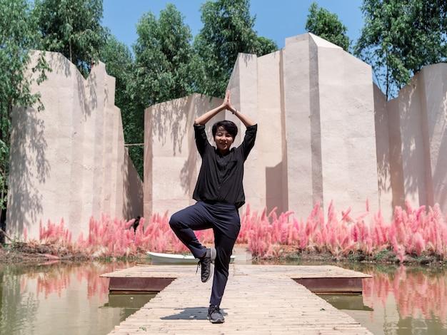 Femmina asiatica lgbt in piedi e fare yoga sul ponte di legno all'aperto nella soleggiata