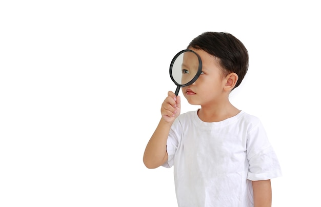 Piccolo neonato asiatico che guarda attraverso una lente d'ingrandimento al lato isolato su fondo bianco con lo spazio della copia
