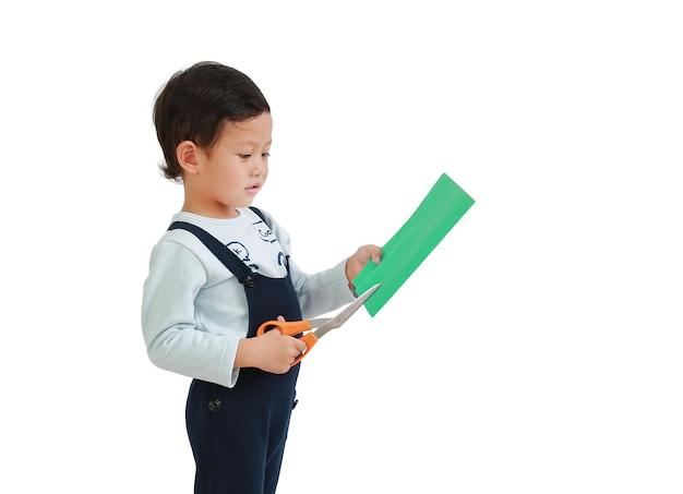 Il ragazzino asiatico si diverte a lavorare con le forbici tagliando la carta colorata isolata su sfondo bianco
