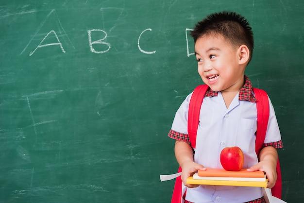 Ragazzino asiatico dall'asilo in uniforme dello studente con il sacchetto di scuola che tiene mela rossa sui libri