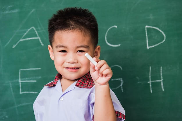 Il sorriso prescolare asiatico dell'asilo del ragazzino in uniforme dello studente tiene il gesso bianco dopo aver scritto abc con sulla lavagna verde della scuola