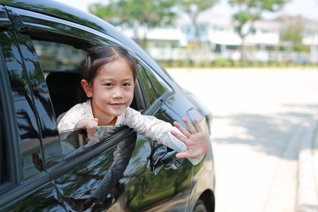 Bambina asiatica in macchina che sorride e guarda la telecamera seduta su un sedile dell'auto salutando con la mano.