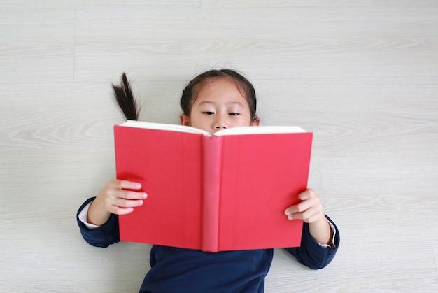 Bambina asiatica bambino in uniforme scolastica casual leggendo il libro e sdraiato sul pavimento in legno laminato