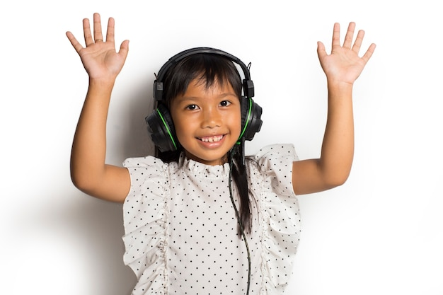 Ragazza asiatica del bambino piccolo che gode della musica. ballare e muoversi esprimendo vere emozioni positive