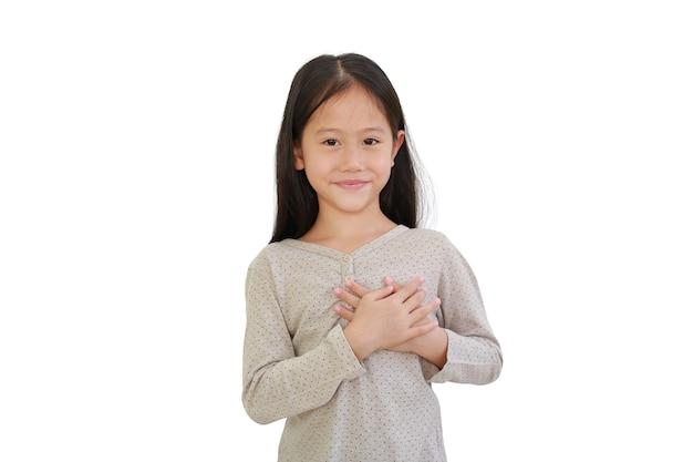 Bambina asiatica che si tiene per mano sul petto isolato su priorità bassa bianca. kid posizionare le braccia sul gesto del cuore d'amore.