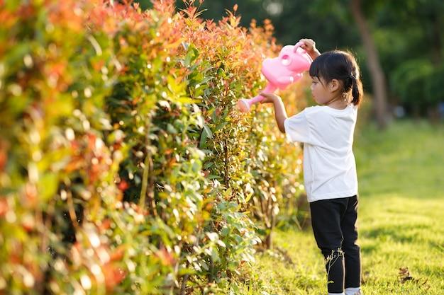 Bambina asiatica che versa acqua sugli alberi il bambino aiuta a prendersi cura delle piante con un annaffiatoio in giardino.