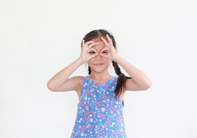 Ragazza asiatica del piccolo bambino con gli occhiali delle mani davanti ai suoi occhi isolati su bianco