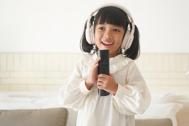 Bambino asiatico che canta felice a casa con le cuffie e un microfono
