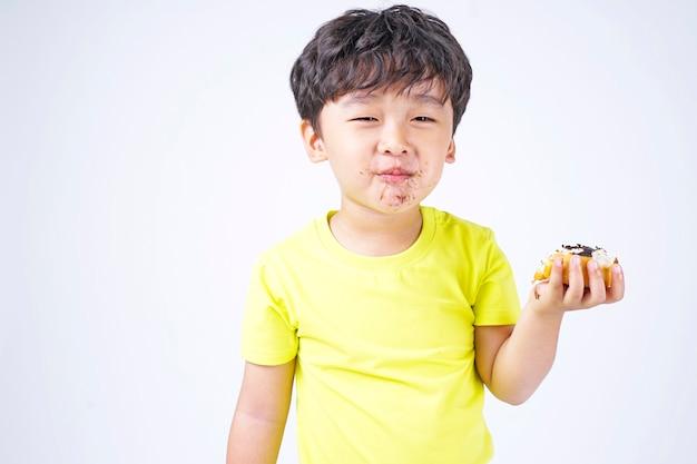 Piccolo ragazzo sveglio asiatico che mangia grande ciambella