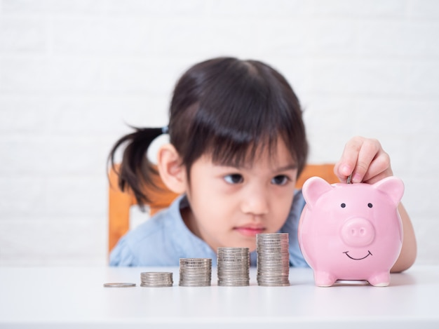 Piccola ragazza sveglia asiatica 4 anni che risparmiano soldi dentro ad un maiale rosa sulla parete bianca fuoco selettivo alle monete.