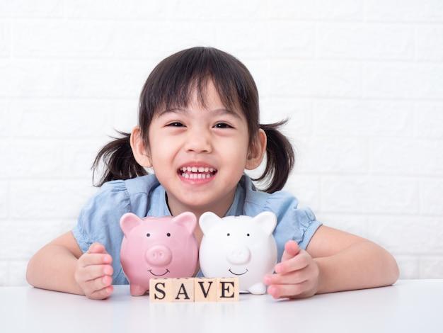 Piccola ragazza sveglia asiatica 4 anni che risparmiano soldi dentro ad un maiale rosa sulla parete bianca