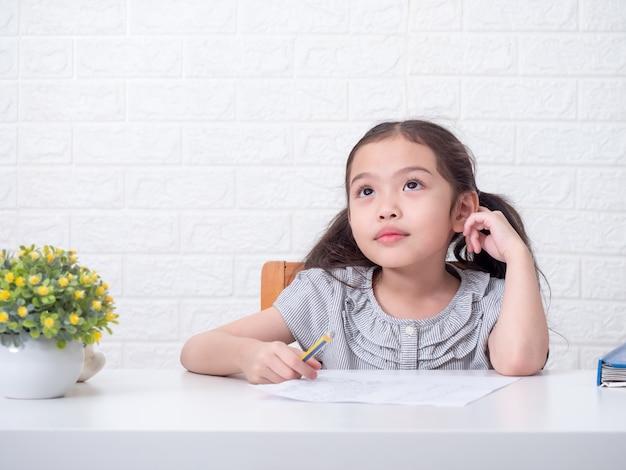 Piccola ragazza sveglia asiatica 6 anni che tiene matita e che pensa ai compiti di matematica sopra il muro di mattoni bianco e la tavola bianca. apprendimento ed educazione