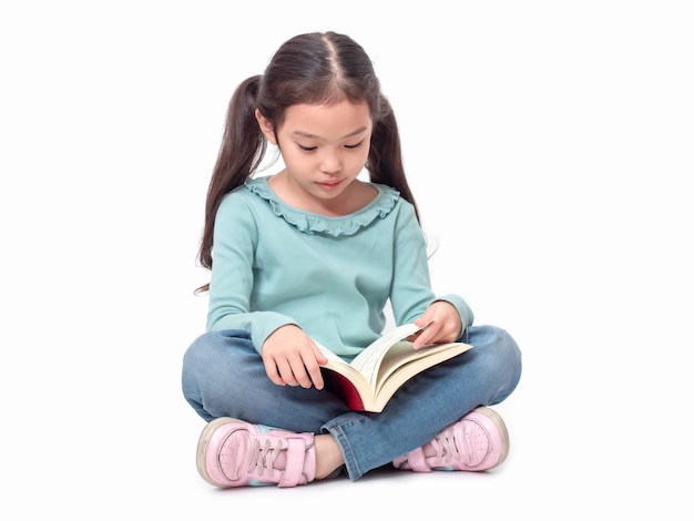 Piccola ragazza sveglia asiatica 6 anni che si siedono sul pavimento e che leggono il libro. bambino adorabile prescolare con il libro.