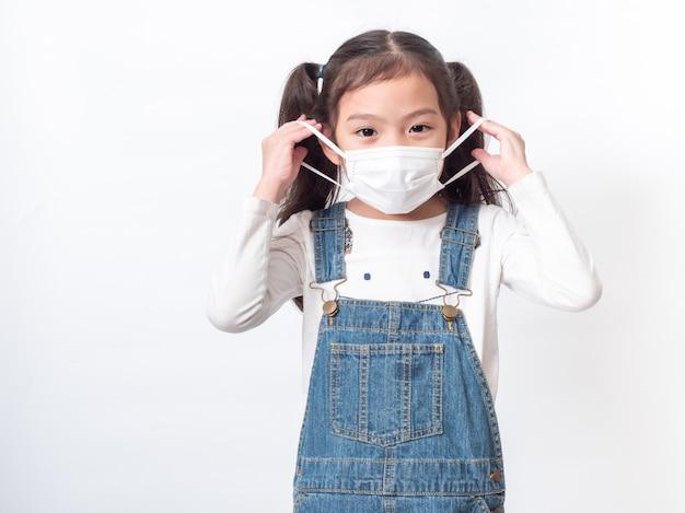 Piccola ragazza carina asiatica di 6 anni che indossa una maschera igienica per proteggere il coronavirus o covid-19 sulla parete bianca.
