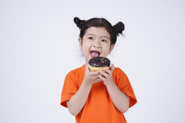 Piccola ragazza sveglia asiatica che mangia grande ciambella
