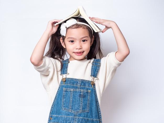 La piccola ragazza sveglia asiatica ha messo il libro sulla testa e sullo sguardo. vista laterale del bambino adorabile prescolare con il libro isolato