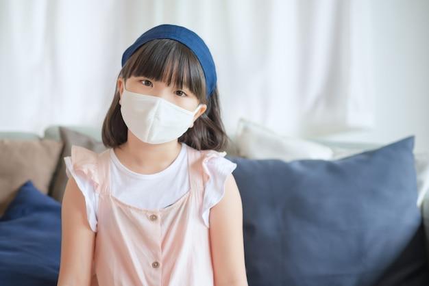 Bambina asiatica carina che indossa una maschera igienica per prevenire l'epidemia di coronavirus o covid-19, mantenere le distanze sociali e rimanere a casa.