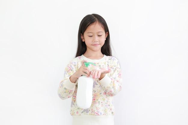 La bambina asiatica applica la lozione nelle mani su bianco