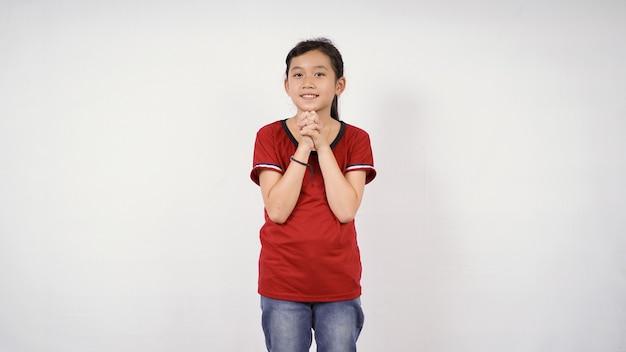 Bambina asiatica che elemosina un desiderio che sorride su fondo bianco isolato
