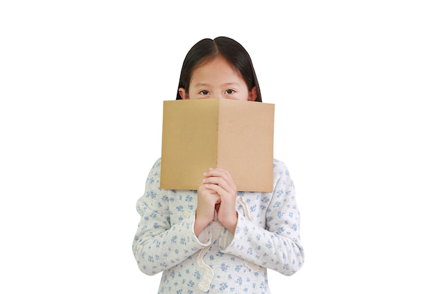 La bambina asiatica che tiene la copertina del libro marrone nasconde la bocca e il naso guardando la telecamera isolata su sfondo bianco. immagine con tracciato di ritaglio