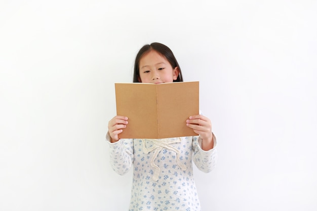 Bambina asiatica che tiene libro marrone e legge su sfondo bianco.