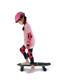 Bambina asiatica pattinaggio su skateboard isolato su sfondo bianco. bambino che guida sullo skateboard.