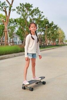 Bambina asiatica pattinaggio su uno skateboard. kid in sella su skateboard all'aperto in strada. lei fa skateboard sulla strada