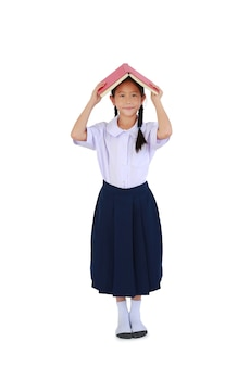 Bambina asiatica in uniforme scolastica tailandese in piedi con la copertina del libro aperta sopra la testa isolata su sfondo bianco. a tutta lunghezza con tracciato di ritaglio